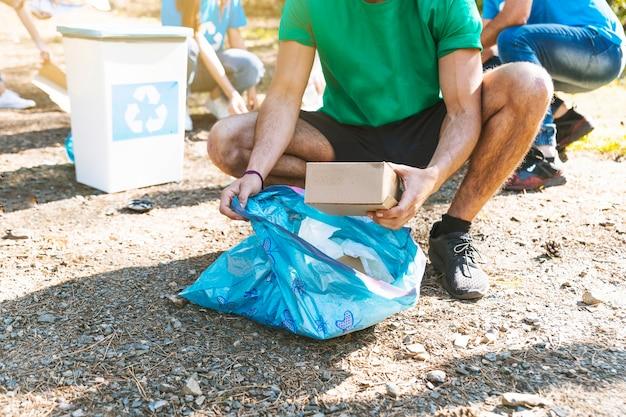Attivista che raccoglie rifiuti nel sacco della spazzatura