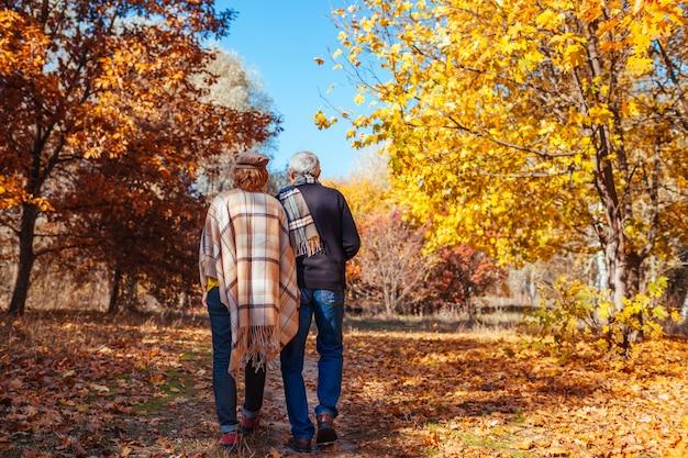 Attività autunnali. coppie senior che camminano nel parco di autunno. uomo e donna di mezza età che abbracciano e che raffreddano all'aperto