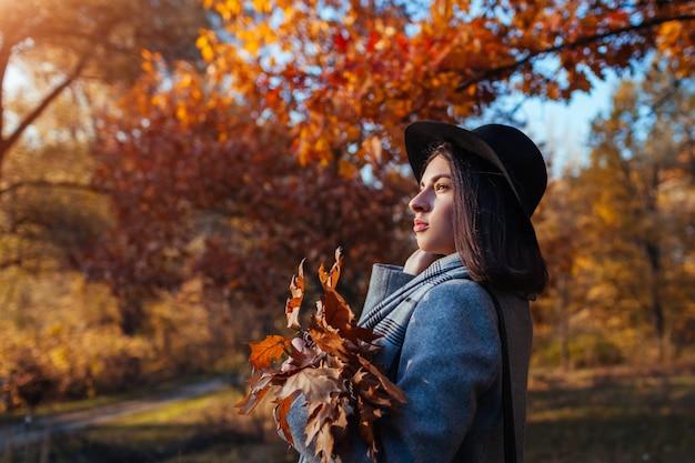 Attività autunnali. giovane donna che cammina nel parco di autunno che indossa vestiti ed accessori alla moda.