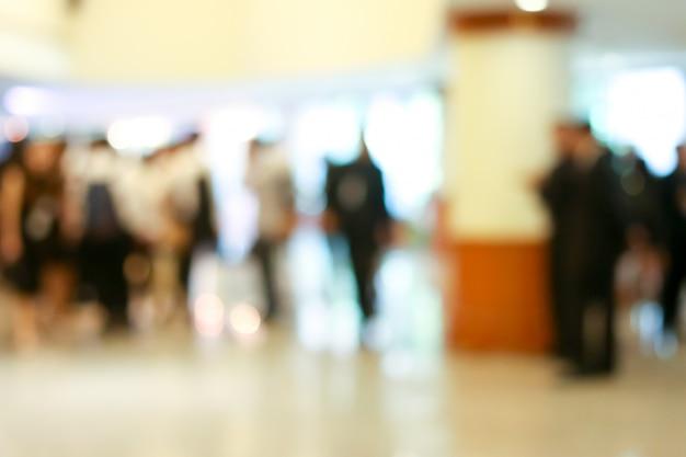 Attività di uomini d'affari in piedi e camminando nella hall offuscata.