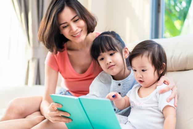 Attività in famiglia. madre asiatica e piccola scrittura sveglia del bambino sul libro che disegna un'immagine con la sorella maggiore.