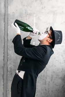 Attore di teatro mimo che beve da una bottiglia grande e interpreta un ubriaco.