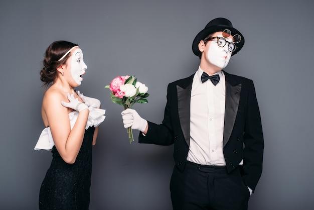 Attori della pantomima che si esibiscono con bouquet di fiori