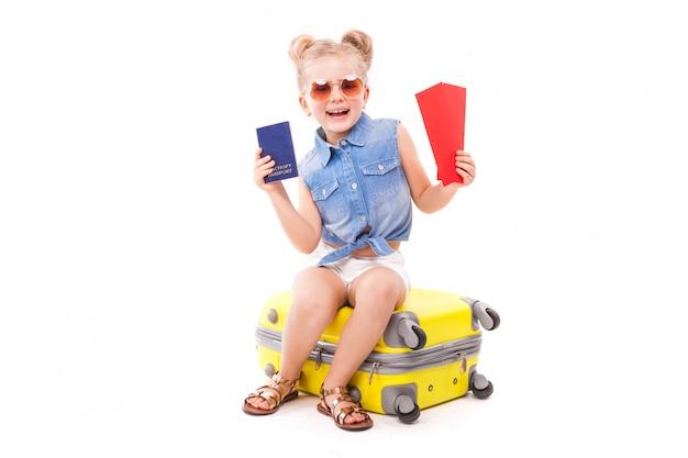 Attraente bambina in camicia blu, pantaloncini bianchi e occhiali da sole sedersi sulla valigia gialla