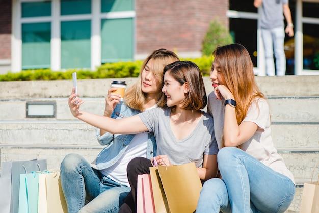 Attraente bella donna asiatica utilizzando uno smartphone mentre lo shopping in città