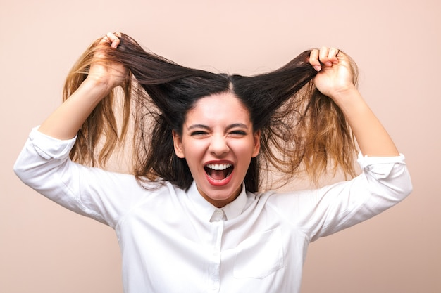 Attraente bruna in camicia bianca tira i capelli e urla. donna che diventa pazza