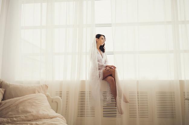 Attraente bruna in pizzo bianco vestito in posa nella cornice della finestra