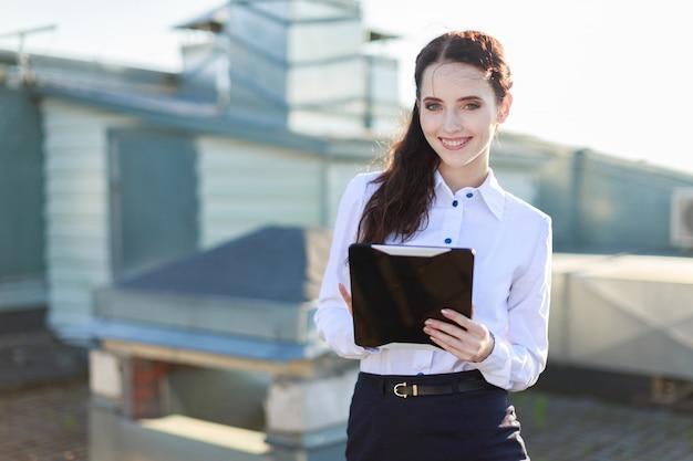 Attraente businesslady in camicetta bianca e gonna nera si posiziona sul tetto e regge un tablet