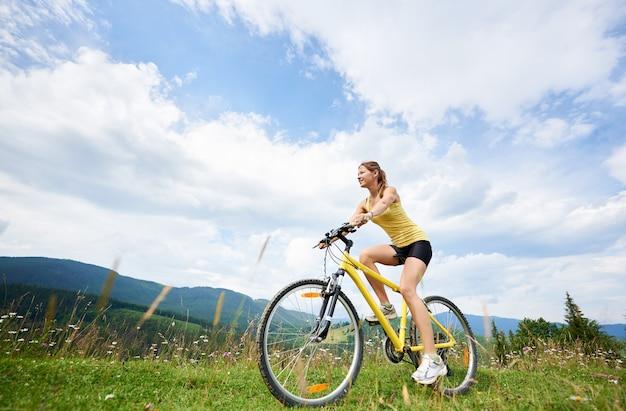 Attraente ciclista donna felice in sella a una bicicletta di montagna gialla su una collina erbosa, godendo la giornata estiva in montagna. attività sportiva all'aperto, concetto di lifestyle