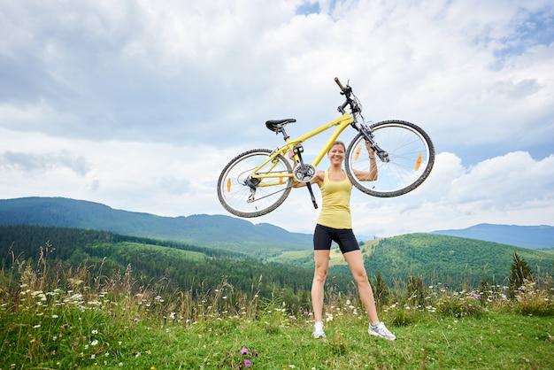 Attraente ciclista femmina con mountain bike gialla, godendo la giornata di sole in montagna
