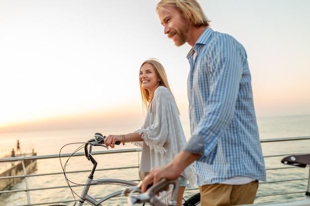 Attraente coppia felice di amici che viaggiano in estate in bicicletta, uomo e donna con moda stile hipster boho capelli biondi divertendosi insieme, camminando in riva al mare nella località turistica