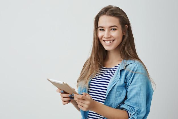 Attraente di bell'aspetto tenero affascinante giovane femmina lifestyle blogger digitando nuovo messaggio online holding tavoletta digitale sorridente ampiamente dando consigli sulla salute internet