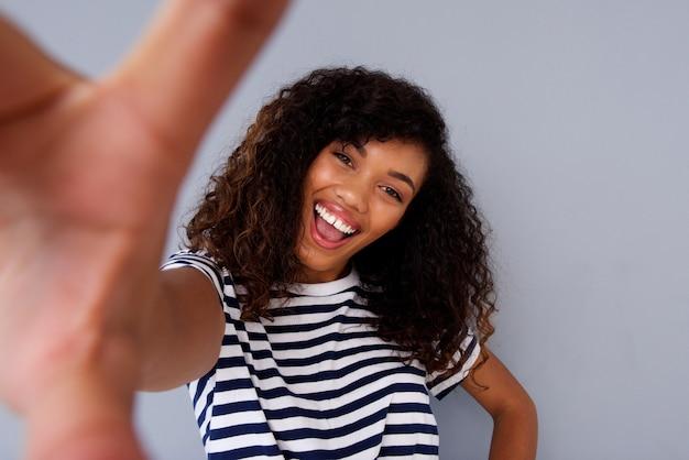 Attraente donna africana sorridente e prendendo selfie