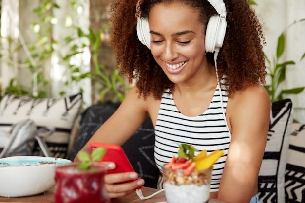 Attraente donna afroamericana positiva con i capelli ricci indossa le cuffie tramite applicazione mobile e chat in rete, connessa a internet wireless, si diverte a divertirsi, legge buone notizie