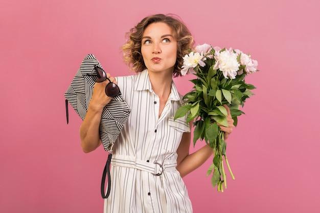 Attraente donna alla moda in elegante abito a righe bianche su sfondo rosa studio espressione emotiva del viso, sorpreso, borsetta, bouquet di fiori, divertente, acconciatura riccia, accessorio di tendenza estiva di moda