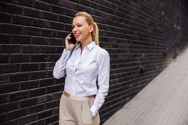 Attraente donna alla moda sorridente che cammina all'aperto e parla al telefono.