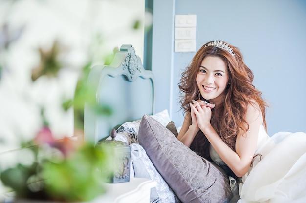 Attraente donna bella sorriso sul letto in abito da sposa