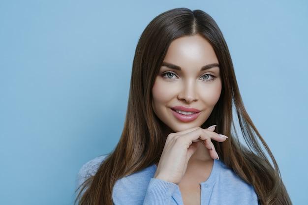 Attraente donna bruna con espressione calma, pelle sana e trucco, tiene la mano sotto il mento