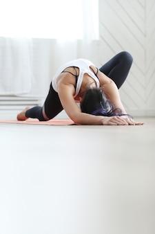 Attraente donna bruna facendo yoga a casa.