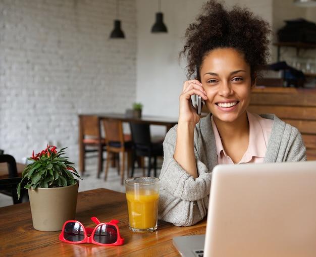 Attraente donna che parla al telefono a casa
