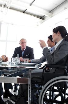 Attraente donna d'affari in una sedia a rotelle durante un incontro
