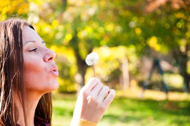 Attraente donna dai capelli lunghi nel parco che soffia un dente di leone