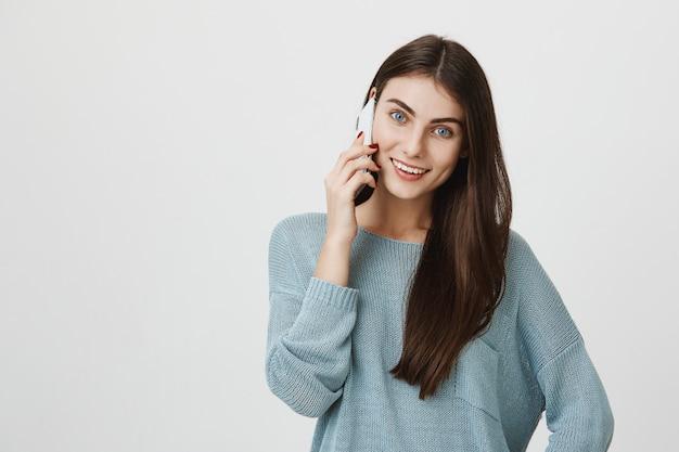 Attraente donna dai capelli scuri che ha conversazione telefonica