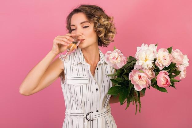 Attraente donna elegante alla data in elegante abito a righe bianche su sfondo rosa studio bevendo champagne in vetro, celebrando, tenendo il bouquet di fiori di peonia, bellissimo stile moda, alcol