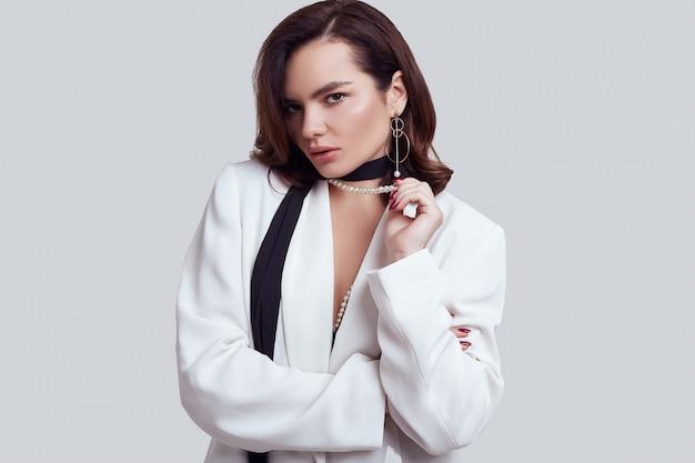 Attraente donna elegante con i capelli scuri in abito bianco di moda