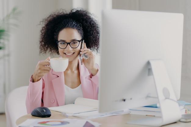 Attraente donna elegante dai capelli ricci beve caffè aromatico, pone sul desktop con computer moderno necessario per il lavoro, chiama amico durante la pausa, discute le ultime notizie, ha un sorriso a trentadue denti