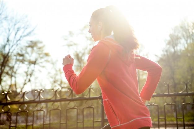 Attraente donna felice che fa jogging nel parco