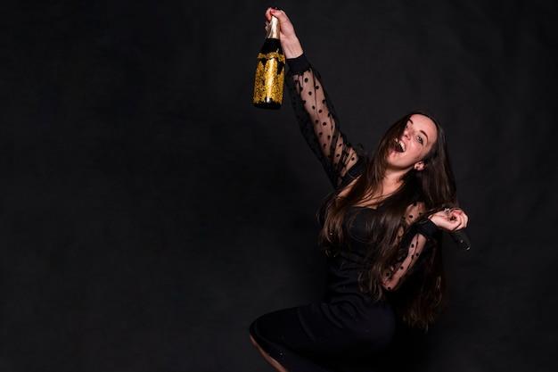 Attraente donna felice in abito da sera con una bottiglia di bevanda
