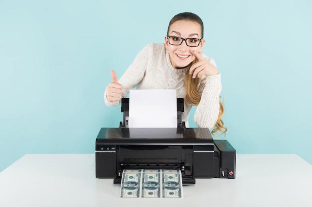 Attraente donna felice in maglione e occhiali tenendo stampante stampa banconote da un dollaro con il pollice in su