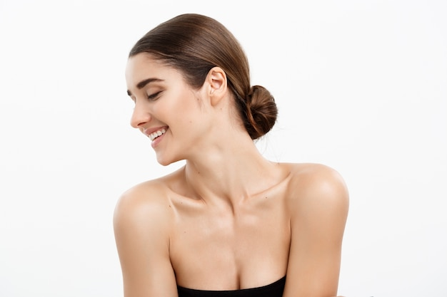 Attraente donna giovane e sana con trucco nude su sfondo bianco.