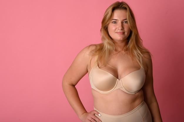Attraente donna grassa con metro a nastro sulla parete rosa