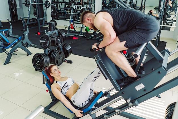 Attraente donna in abiti sportivi bianchi fa esercizi per le gambe con un uomo su un moderno simulatore in palestra. la ragazza va per gli sport con personal trainer in palestra.