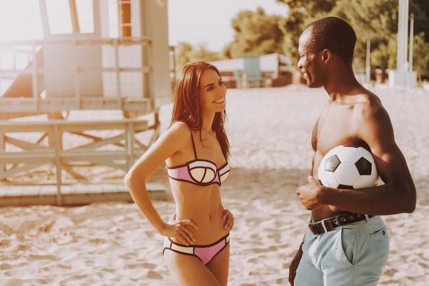 Attraente donna in bikini parlando con guy