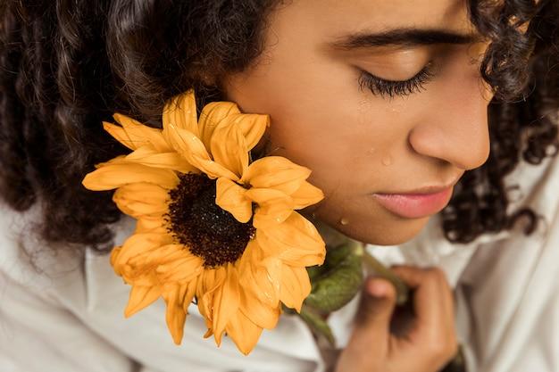 Attraente donna piangente etnica con fiore