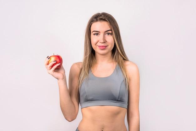 Attraente donna positiva con la mela
