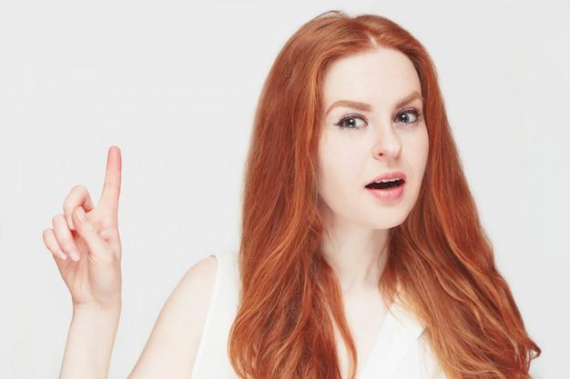 Attraente donna rossa ha un avviso o un'idea per te.