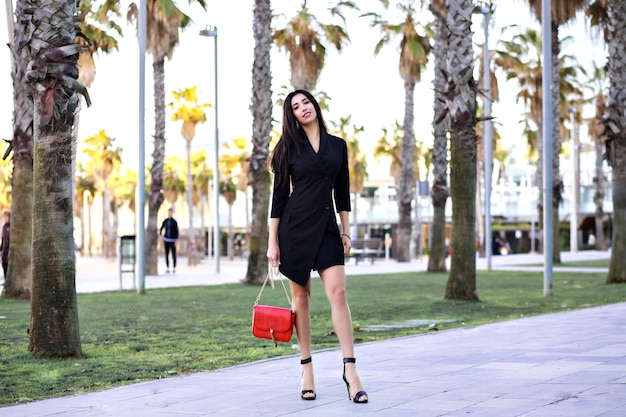 Attraente donna sicura di sé sexy che cammina per strada con palme, vestito nero minimalista da donna di affari moderna, viaggiando in spagna.