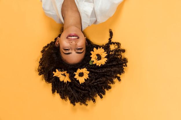 Attraente donna sorridente etnica con fiori sui capelli
