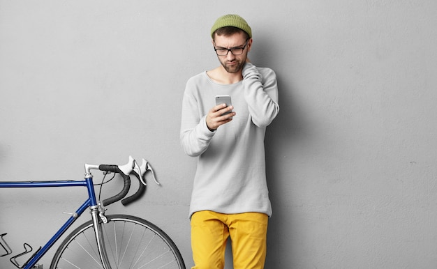 Attraente giovane bruna con la barba che ha un'espressione confusa o perplessa sul suo viso mentre riceve un messaggio urgente sull'e-mail dal suo capo, utilizzando la connessione internet 3g sul telefono cellulare