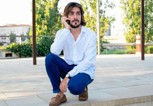 Attraente giovane con la barba, con camicia bianca parla al suo smartphone con la faccia seria.