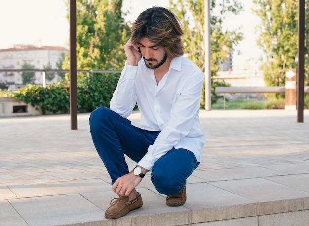Attraente giovane con la barba, con camicia bianca parla con il suo smartphone.