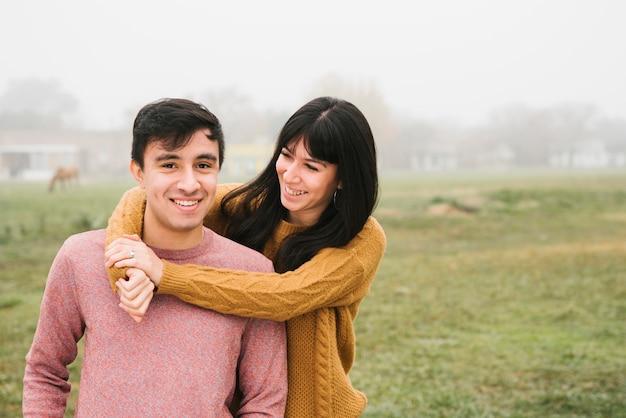 Attraente giovane coppia in piedi in un abbraccio