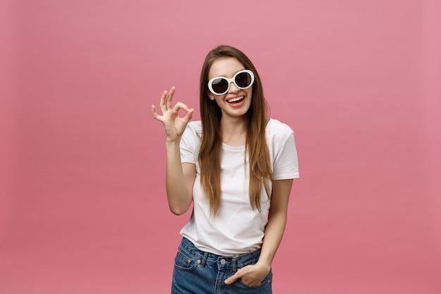 Attraente giovane donna adulta mostrando segno ok