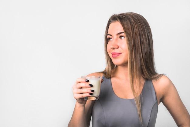 Attraente giovane donna allegra in abiti sportivi con un bicchiere di latte