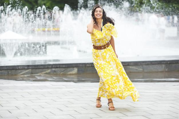 Attraente giovane donna che cammina in città. signora in abito lungo giallo vicino alla fontana. bella femmina su sfondo estivo.