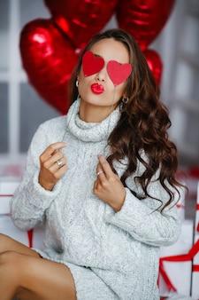 Attraente giovane donna con doni e palloncini